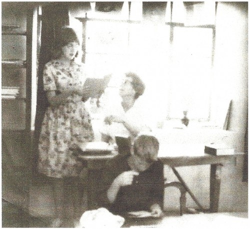 "The photograph above was taken in about 1965 inside the Presbyterian Church in Jemez Springs, where the original library was located before moving to a ""donated"" room in the Jemez Mountains Electric Coop building. Patricia Evilsizer (assistant librarian) stands next to Grace Swetnam, seated. Jim Swetnam is at the table in the foreground. In addition to Patricia, Lupe Casaus also served volunteered as an assistant librarian."