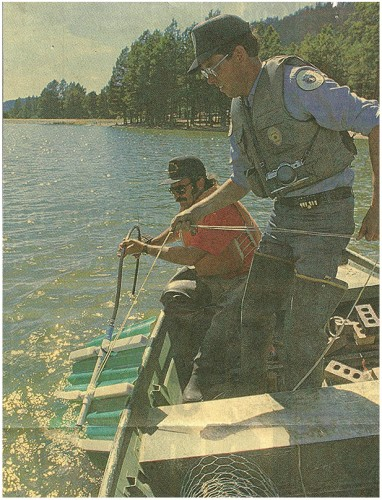 Game and Fish officer Jack Kelly and T.J. Jimerson lower a diffuser into the depths of Fenton Lake in the Jemez Mountains. Photo by Bill Dyroff/Journal