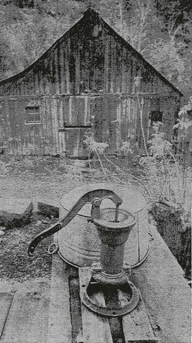 Barn with Dutch doors stands behind pump which still supplies water
